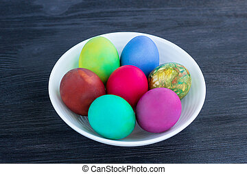 White plate with Easter multicolored eggs on black wood