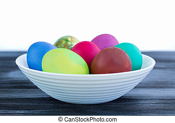 White plate with Easter multicolored eggs on black wooden background