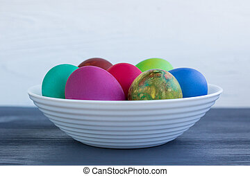 White plate with Easter multicolored eggs on grey wood