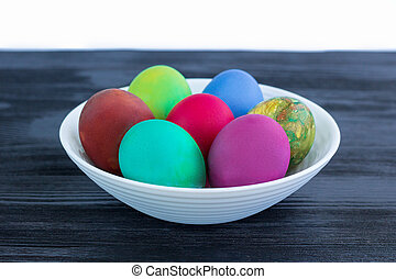 White plate with Easter versicolored boiled eggs on black wood