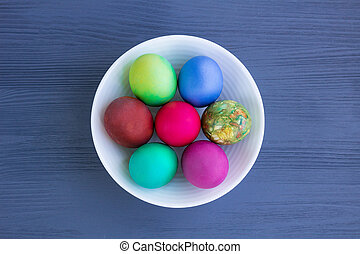 White plate with Easter versicolored eggs on grey wooden background