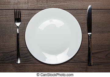 white plate with knife and fork on wooden table