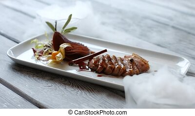 White plate with meat. Meat dish on wooden background. Duck...