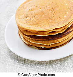White plate with pancakes stack on the kitchen table