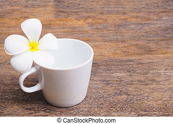 White plumeria flower and empty cup of coffee