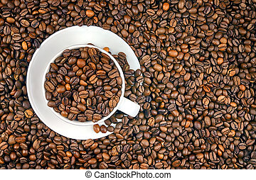 White porcelain cup and whole coffee grains background. ...