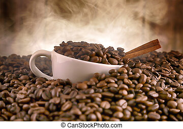 White porcelain cup in whole coffee grains with cinnamon ...