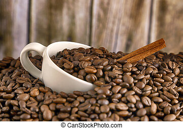 White porcelain cup in whole coffee grains with cinnamon stick, smoke and wooden background. Conceptual image for lovers of delicious coffee.