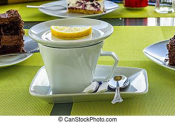 White porcelain cup of tea with lemon, sugar, spoon on a table in the cafeteria.