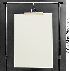 White poster hanging at a clothes rack. - White poster...
