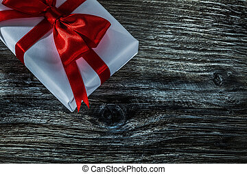 White present box with red bow on wooden board