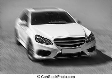 white prestigious car goes on road