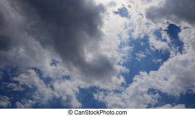 White puffy clouds move across a brilliant blue sky in...