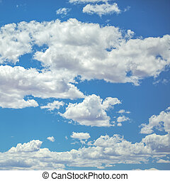 White puffy clouds on a vivid blue sky