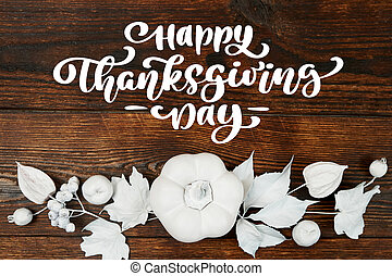White pumpkin, berries and leaves on a wooden autumn background with text Happy Thanksgiving Day. Mockup Greeting card for Thanksgiving Day in rustic style . Flat lay. Top view