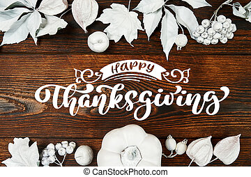 White pumpkin, berries and leaves on a wooden autumn background with text Happy Thanksgiving. Mockup Greeting card for Thanksgiving Day in rustic style . Flat lay. Top view