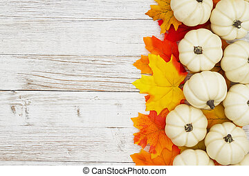 White pumpkins with fall leaves on weathered whitewash wood textured background