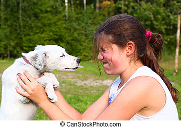 white puppy lick teen girl at face