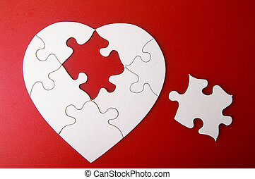 white puzzle heart shape with missing piece, on red