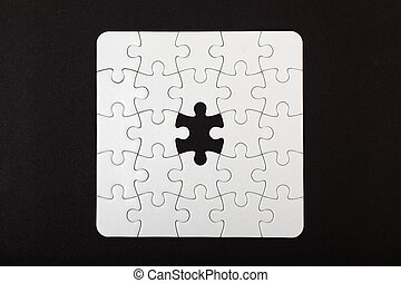 White puzzle with one missing piece on black background