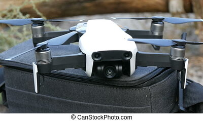 White quadrocopter drone or standing on the bag on nature...