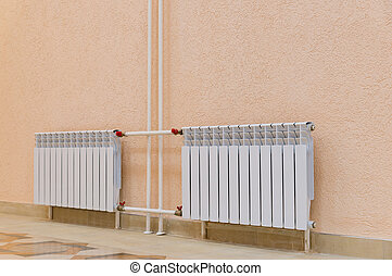 White radiators on pink wall in building