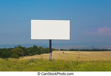 billboard near road against the sky