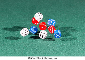 White, red and blue dices falling on a green table