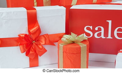 White red gift boxes with gold ribbons and word Sale pan shot