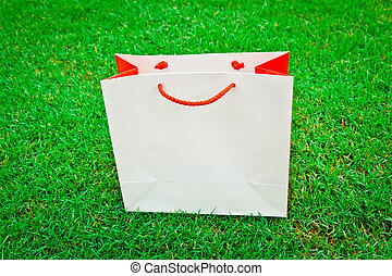 white red shopping bag on green grass