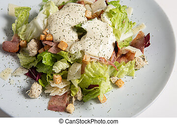 White Restaurant Plate of Caesar Salad with Chicken, Homemade Anchovies Sauces, Croutons, Tomatoes, Greens. Beautiful Delicacy Cesar Salat on Natural Dark Stone and Leaves Background