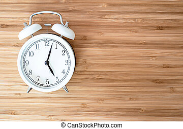 White retro alarm clock on brown wood desk with copy space