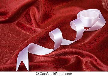 White ribbon on red drape