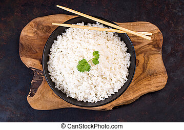 White rice on a black plate with chopsticks on a wooden table.