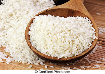 White Rice - Uncooked white rice in a wooden spoon. Shallow ...