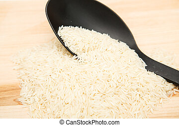 White Rice with Black Spoon on Wood Cutting Board