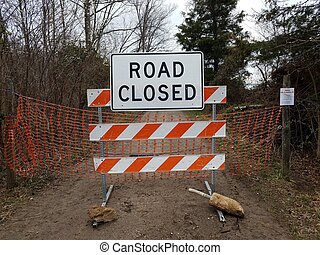 white road closed sign and striped barricade with trail or path