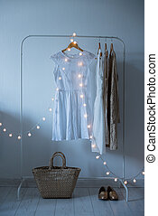 Summer dress, vintage wooden door, basket and decorative lights, girl's room interior decoration with white walls and floors.