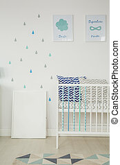 White room with baby cot, wall posters and pattern rug