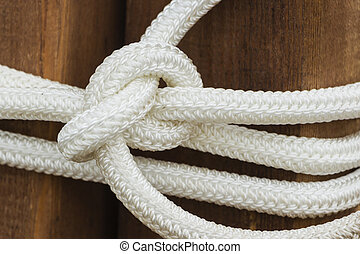 White rope with a knot on wooden background.