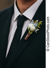 White rose and blue flowers boutonniere on groom's  black suit w