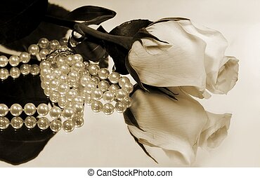 Beautiful white rose and strand of pearls reflected on mirror; sepia toned