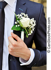 white rose boutonniere on suit of the groom