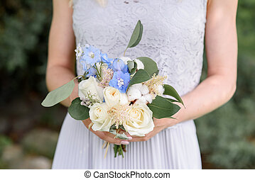 White roses and blue flowers in the bouquet of the bridesmaid.