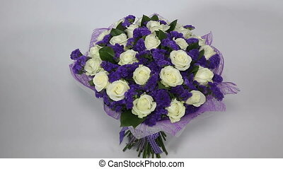 White roses flowers bouquet with violet decor turns