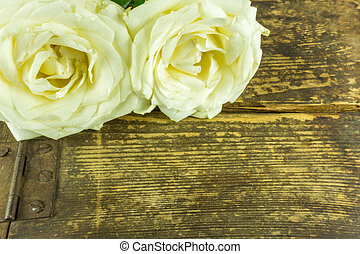 White roses on a rustic wooden table