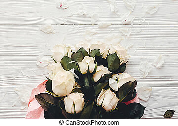 White roses on wooden background, flat lay with space for text. Floral greeting card mockup. Wedding invitation or happy mother day concept. Bouquet of white flowers with petals