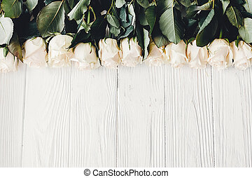 White roses on wooden background, flat lay with space for text. Floral greeting card mockup. Wedding invitation or happy mother day concept. Stylish bouquet of white flowers