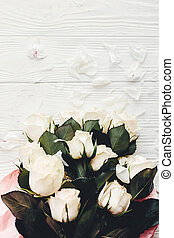 White roses on wooden background, space for text. Floral greeting card mockup. Valentines or happy mother day concept. Bouquet of white flowers with petals