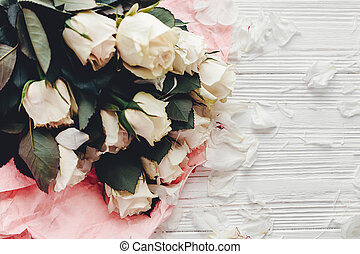 White roses on wooden background, space for text. Floral greeting card mockup. Wedding invitation or happy mother day concept. Bouquet of white flowers with petals